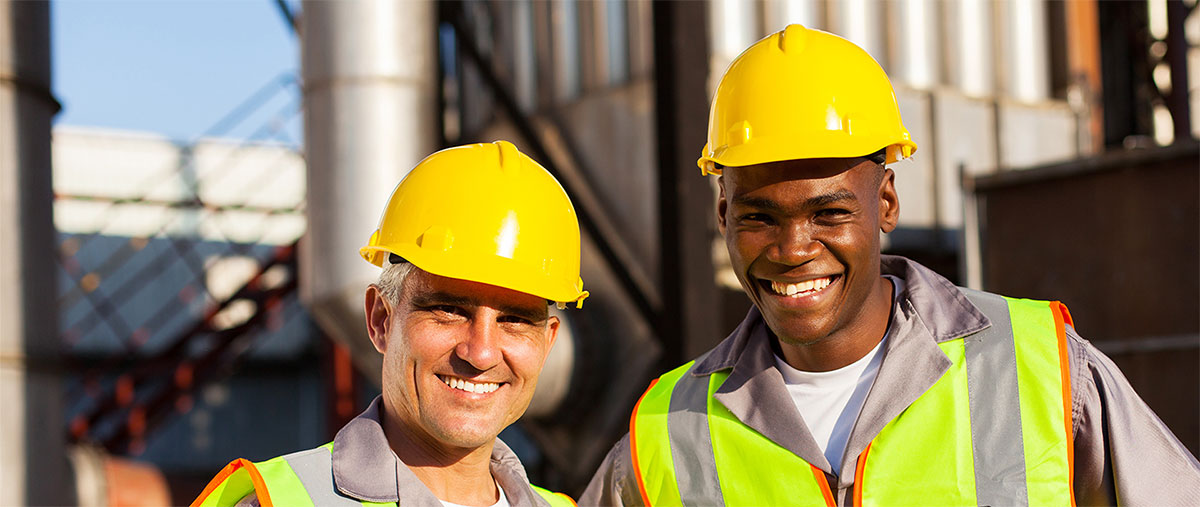 Two smiling men in safety gear outside a plant